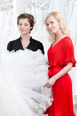 Two girls stare at the wedding dress hesitating about fitting