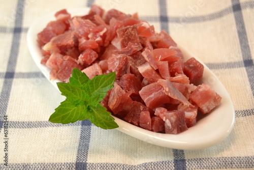 Serrano ham  diced for cooking on a white dish