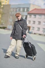 Un jeune homme trisomique avec valise