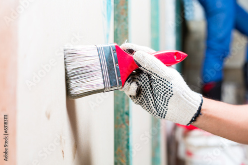 Painter with brush and paint on construction site