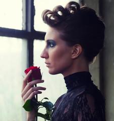 Beautiful elegant woman holding red rose