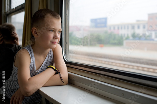 Boy looking out the window moving train