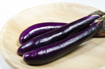 Three Asian Eggplants On A Bamboo Plate