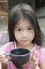 Little Asian girl with a cup of cocoa.