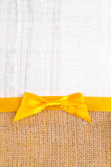 Sackcloth with color ribbon and bow on wooden background