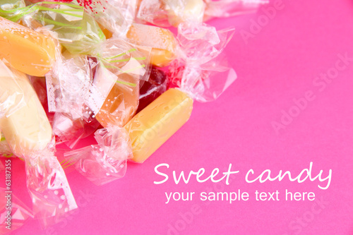 Tasty candies on pink background