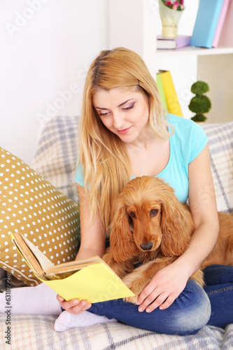 Beautiful young woman with cocker spaniel on couch in room