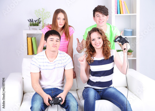 Group of young friends playing video games at home