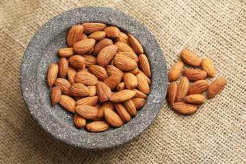 Almonds in bowl on sackcloth background