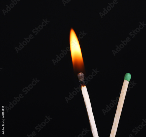 Burning match isolated on black