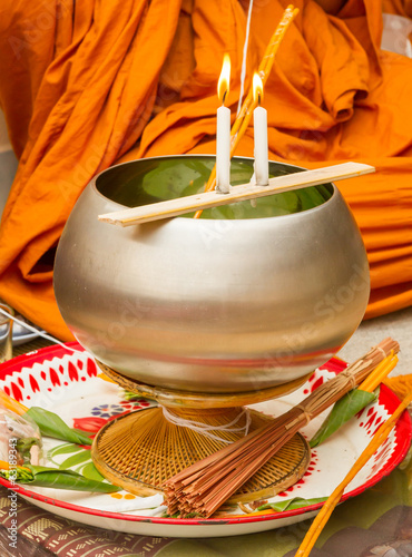 Buddhist monks, bowl with a candle and holy water