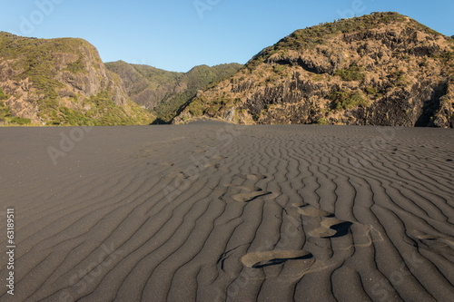 footprints accross black sand dune