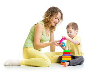 kid boy and mother play together with pyramid toy
