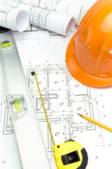 Safety orange helmet and level on project drawings