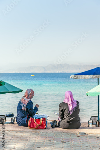 Two arab women lunch at seaside