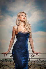 Fashion beautiful young woman in blue dress posing outdoor