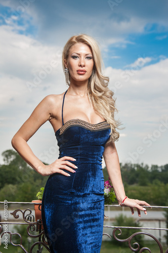 Fashion beautiful young woman in blue dress posing outdoor