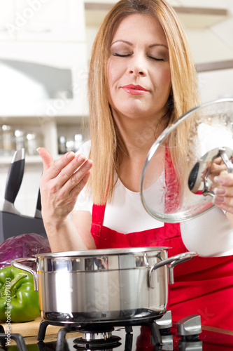 Beautiful housewife cooking and testing the food in  kitchen