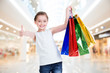 canvas print picture - Pretty smiling little girl with shopping bags