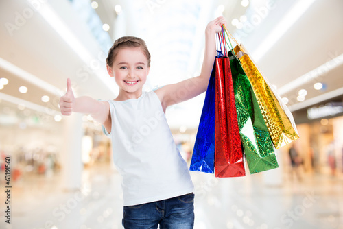 canvas print picture Pretty smiling little girl with shopping bags