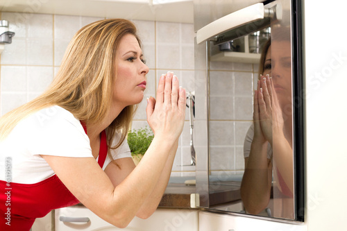 beautiful caucasian woman in a kitchen waiting with anxiety in f