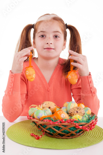 beautiful little red-haired girl with pigtails holding Easter e