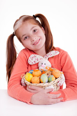 young smiling freckles girl holding a basket of Easter eggs