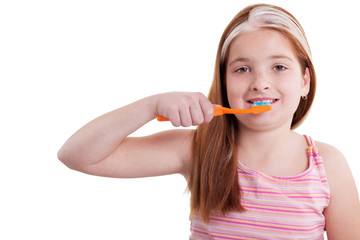 Smiling little girl with freckles  brushing teeth