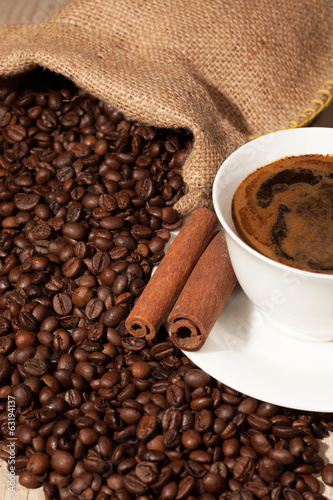 Coffee beans in burlap sack and cup of coffee