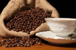 Coffee beans in burlap sack against dark background
