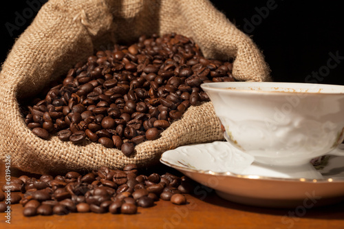 Coffee beans in burlap sack against dark background