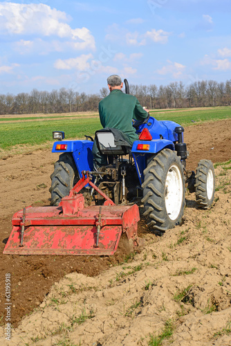 Farmer on tractor handles field