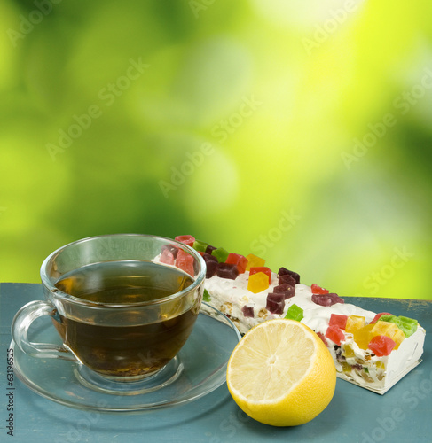 image of tea, lemon and cake on a green background