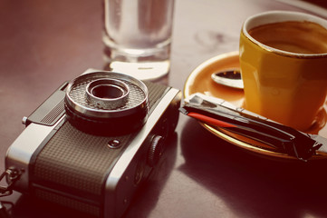 Empty cup of coffee and retro camera