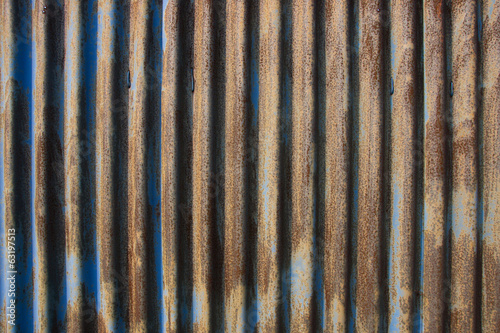old wall from wave plate with rust and parts of blue color