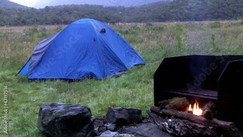 An outdoor campfire near a tent in a countryside campground.