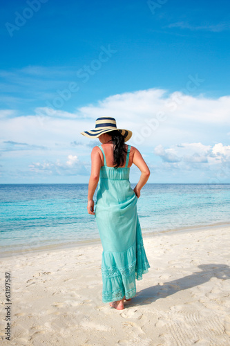 Girl walking along a tropical beach in the Maldives.