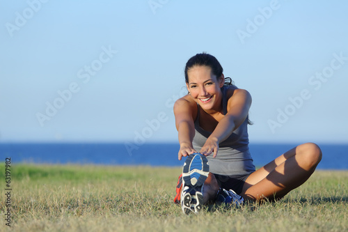 Fitness runner woman stretching on the grass