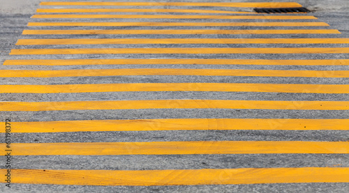 Pedestrian crossing road marking with yellow stripes on asphalt