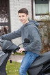 Handsome young teenage boy on a scooter