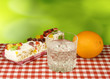 image of a glass of water, orange and cake