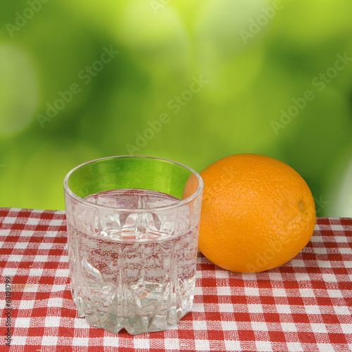 image of a glass of water and orange on green background