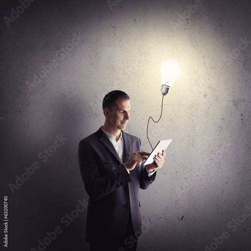 Businessman working with tablet computer and having some idea