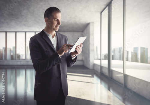 Businessman with tablet computer standing in bright office