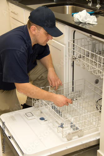 Plumber fixing dishwasher