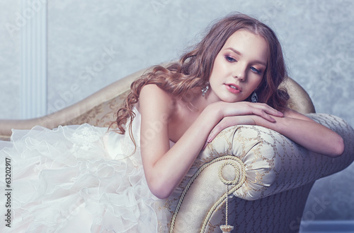 beautiful bride posing in antique sofa, wedding dress, long curl