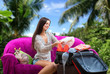 Girl packs suitcase and dreams of vacation, tropical background