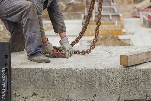Builder worker preparing concrete profile for crane lifting 2