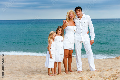 Family in white on beach.
