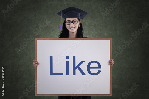 Asian female graduate holding like board in class